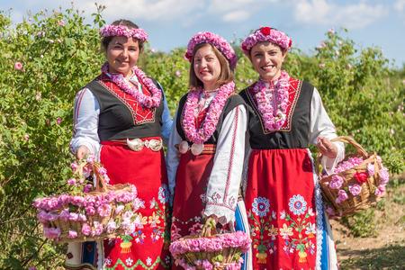 mujer con rosas: Mujer vestida con unas rosas búlgaras picking folclore traje tradicional en un jardín, como parte del ritual regional de verano en Valle de las Rosas, Bulgaria.
