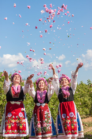 Women dressed in a Bulgarian traditional folklore costume picking roses in a garden, as part of the summer regional ritual in Rose valley, Bulgaria.