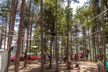 away from it all: KUKLEN, BULGARIA - JUKY 04, 2015 - Forest, music festival near Kuklen village, Bulgaria. People camping and participating in different activities like pottery, yoga, air yoga, handmade jewelry etc.