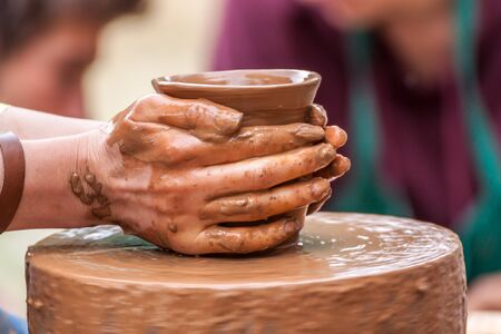 Close-up of hands making pottery