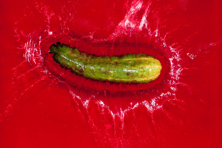 red water: Green cucumber falling into red water and creating a splash Stock Photo