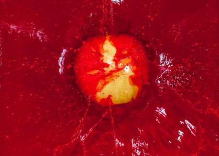 red water: Yellow apple falling into red water and creating a splash