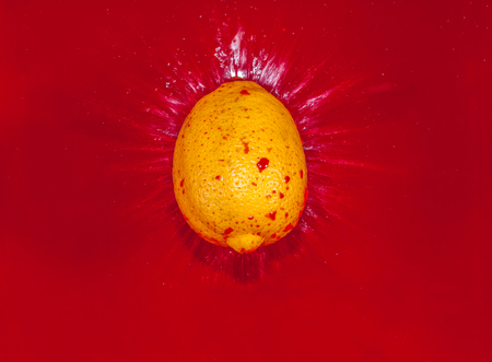 red water: Yellow lemon falling into red water and creating a splash