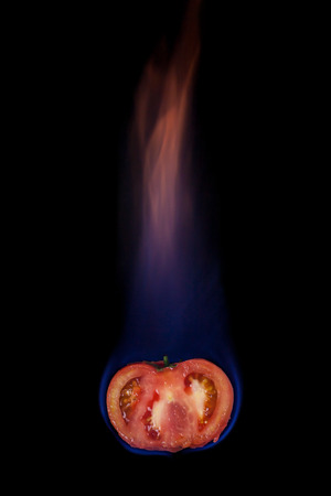 Tomato on fire with blue flames isolated on black background