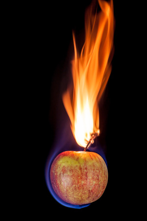 blue flames: Apple on fire with blue flames isolated on black background