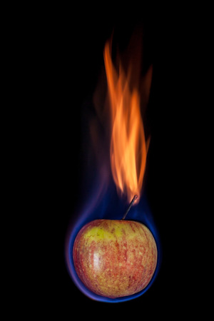 abstract fire: Apple on fire with blue flames isolated on black background