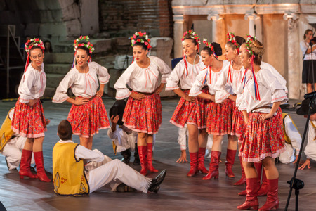 show folk: PLOVDIV, BULGARIA - AUGUST 06, 2015 - 21-st international folklore festival in Plovdiv, Bulgaria. The folklore group from Serbia dressed in traditional clothing is preforming Serbian national dances.