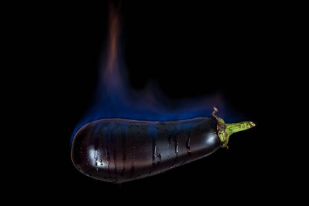 blue flames: Eggplant on fire with blue flames isolated on black background
