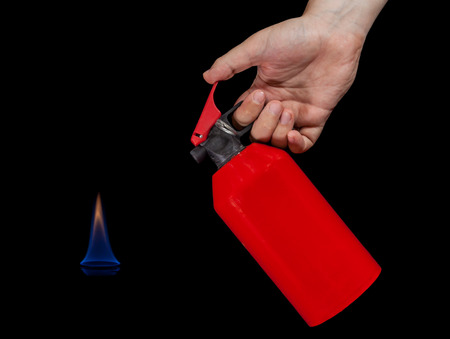 flame background: Human hand holding fire extinguisher and a blue flame isolated on black background