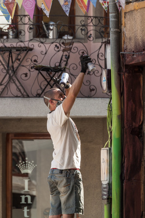 youth crime: PLOVDIV, BULGARIA - SEPTEMBER 19, 2015 - Kapana street festival in Plovdiv, Bulgaria. Young people painting graffiti and decorating the streets of Kapana area in Plovdiv.