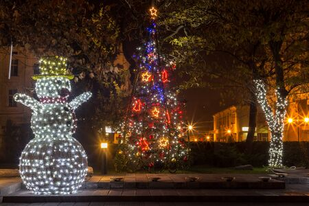 no people: Snowman statue decorated with a lot of lights. Stock Photo