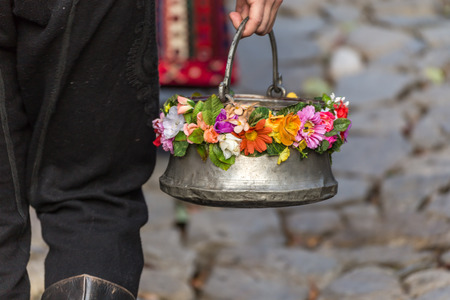 bronze bowl: Bulgarian traditional pot called menche, decorated with some flowers Stock Photo