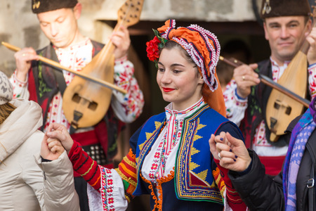 accompanied: PLOVDIV, BULGARIA - NOVEMBER 29, 2015 - Young wine parade in the Old Town in Plovdiv, Bulgaria. Public wine tasting accompanied with traditional folklore dances.