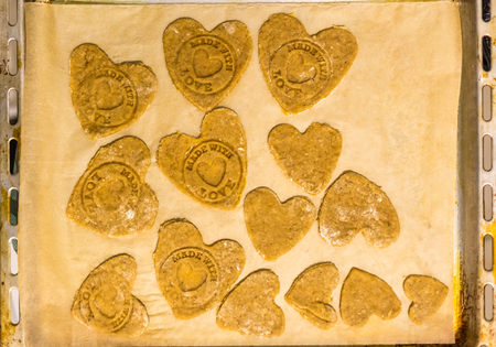 love stamp: Heart shaped cookies on a baking paper with made with love stamp on them