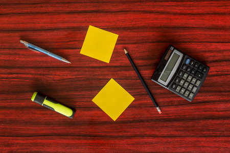 veiw: Areal veiw of pen, pencil, calculator and yellow notes on a desk