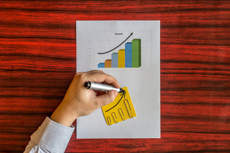 left handed: Left handed person drawing an arrow on a yellow note Stock Photo