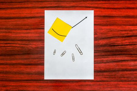 paper clips: Curve graph printed on a sheet of paper and yellow note with spreaded paper clips