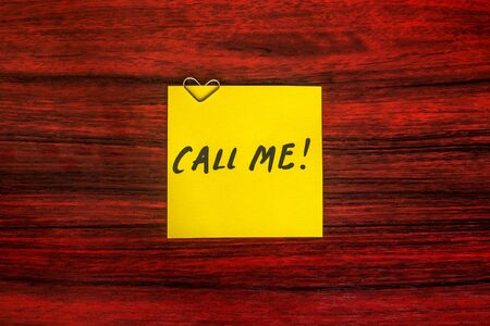 call me: Heart shaped paper clip on a yellow sticky note with the words Call me written on it. Stock Photo