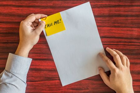attached: Hands holding blank page with yellow note attached by heart shaped paper clip.