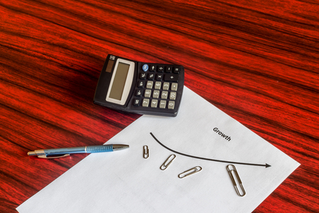 paper clips: Different sized Paper clips arranged around a curve graph symbolising business growth. Calculator and a pen lying aside. Stock Photo