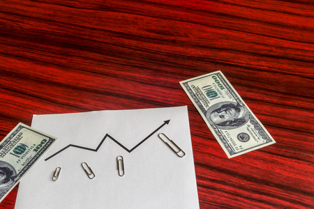 paper clips: Curve graph printed on a sheet of paper with arranged by size paper clips and dollar bills.