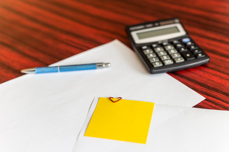 attached: Heart shaped paper clip attached to a sheet of paper with a yellow sticky note. Calculator and pen laying aside Stock Photo