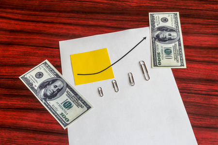 paper clips: Curve graph printed on a sheet of paper and yellow note with arranged by size paper clips and dollar bills.