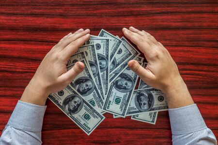 Hands grabbing money from a desk Stock Photo