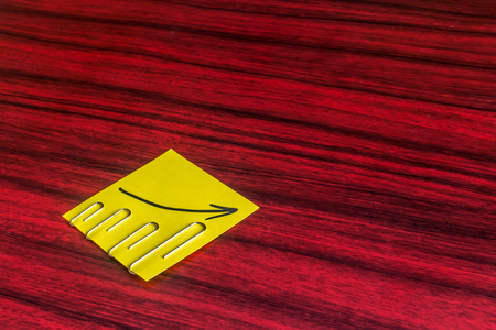 stapled: Paper clips attached by size on a yellow note with an arrow written on it.
