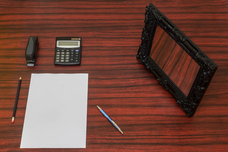 blanck: Blanck sheet of paper on a desk with pen, pencil and calculator around it