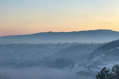 colorful sunrise: Foggy and colorful sunrise above Pernik city, Bulgaria. Stock Photo