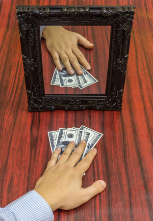 taking risks: Human hand taking money from a table in front of a mirror