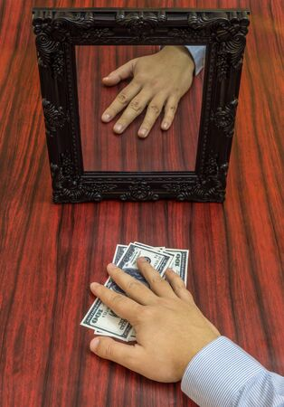 taking risks: Human hand holding money without reflection in the mirror.