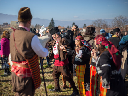 the fruitful: PERUSHTITSA, BULGARIA - FEBRUARY 14, 2015 - Recreating the ritual called Zariazvane in Perushtitsa, Bulgaria. People dressed in traditional clothing dance and cut the vineyards for fruitful harvest.