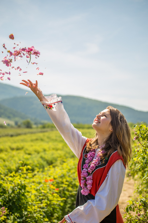 Bulgarian girl dressed in traditional clothing throwing rose in the air during the Annual Rose Festival in Kazanlak, Bulgaria