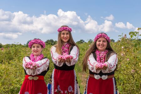 Three Bulgarian girls dressed in traditional clothes giving roses. Looking directly at the camera with a bright blue sky in the background.