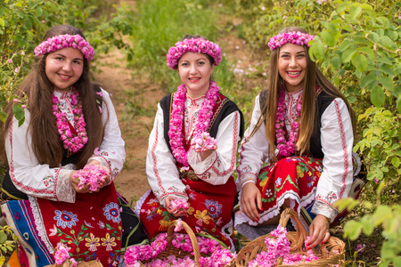 Bulgarian girl dressed in traditional dress picking roses and having fun during the Annual Rose Festival in Kazanlak, Bulgaria Stock Photo