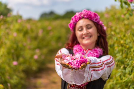 looking directly at camera: Bulgarian girl dressed in traditional clothes giving roses. Looking directly at the camera. Stock Photo