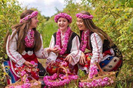 Bulgaars meisje, gekleed in traditionele kleding picking rozen en plezier tijdens de jaarlijkse Rozenfestival in Kazanlak, Bulgarije