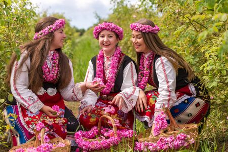 Bulgarian girl dressed in traditional dress picking roses and having fun during the Annual Rose Festival in Kazanlak, Bulgaria Фото со стока