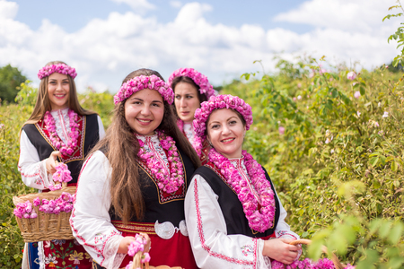 Three Bulgarian girls dressed in traditional dress picking roses during the Annual Rose Festival in Kazanlak, Bulgaria Stock Photo