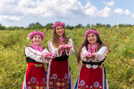 bulgaria girl: Three Bulgarian girls dressed in traditional clothes giving roses. Looking directly at the camera with a bright blue sky in the background.