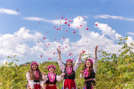 Four Bulgarian girls dressed in traditional clothing throwing rose in the air during the Annual Rose Festival in Kazanlak, Bulgaria