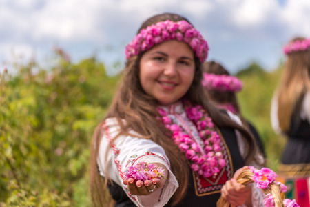 Bulgarian girl dressed in traditional clothes giving roses. Looking directly at the camera. Stock Photo