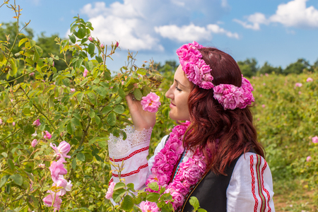 Bulgarian girl dressed in traditional clothing feeling the aroma of a rose during the Annual Rose Festival in Kazanlak, Bulgaria