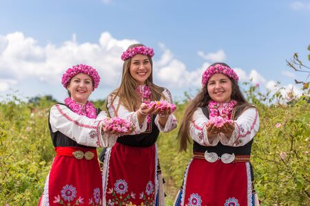 looking directly at camera: Three Bulgarian girls dressed in traditional clothes giving roses. Looking directly at the camera with a bright blue sky in the background.