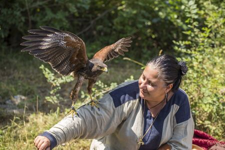 ASENVOGRAD, BULGARIA - JUNE 25, 2016 - Medieval fair in Asenovgrad recreating the life of Bulgarians during the Middle ages. Woman with a trained falcon.