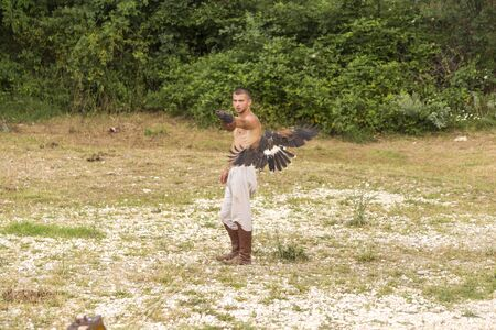 commands: ASENVOGRAD, BULGARIA - JUNE 25, 2016 - Medieval fair in Asenovgrad recreating the life of Bulgarians during the Middle ages. Young man training a falcon to various commands.