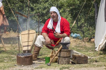 medieval blacksmith: ASENVOGRAD, BULGARIA - JUNE 25, 2016 - Medieval fair in Asenovgrad recreating the life of Bulgarians during the Middle ages. Blacksmith making a small envelop opener knife .