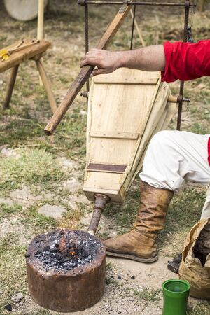medieval blacksmith: ASENVOGRAD, BULGARIA - JUNE 25, 2016 - Medieval fair in Asenovgrad recreating the life of Bulgarians during the Middle ages. Blacksmith melting a piece of metal in a small forge. Editorial
